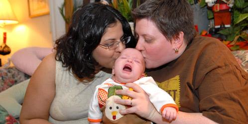 Kimberly y Jessica Kenny sostienen a su hija Olivia Kenny, en su apartamento de Queens. (Corbis)